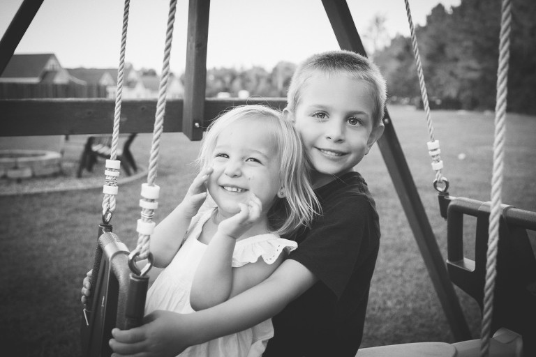 brother and sister on swings in backyard