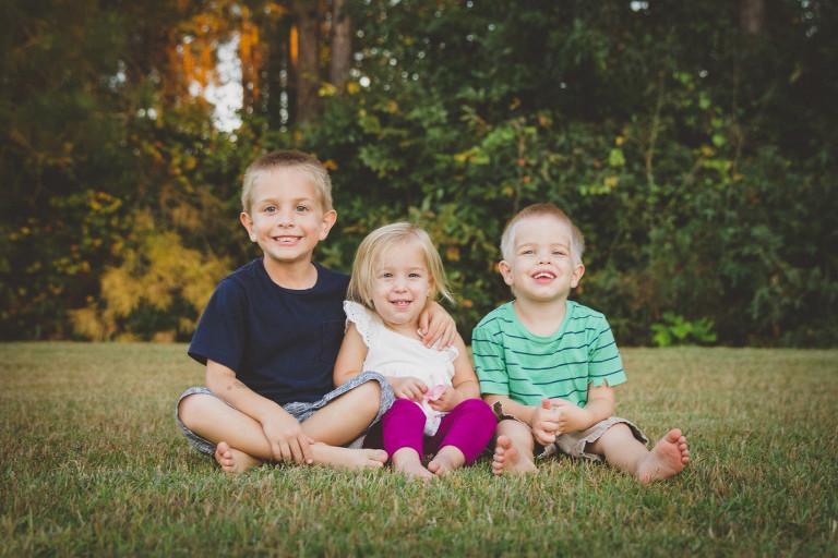 three siblings sitting in their backyard in Hampstead NC