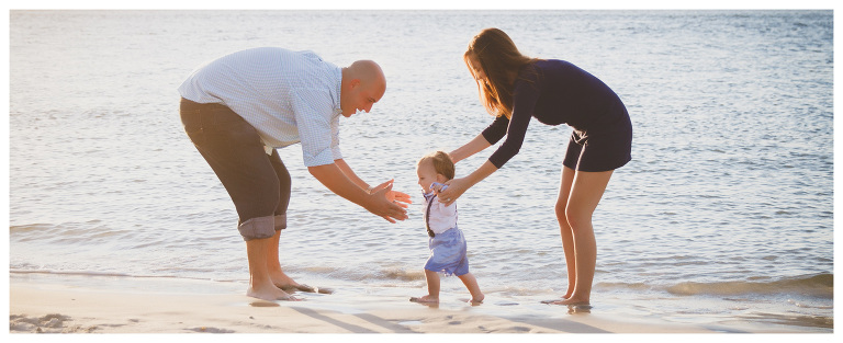 mom dad and baby playing on the beach for family photos