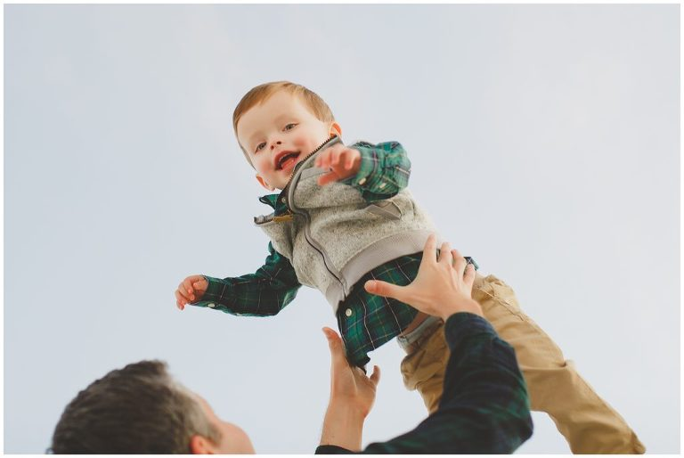 winter sky, dad tossing his smiling little boy into the air, green plaid shirt, fleece vest, khaki toddler boys pants